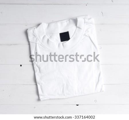 folded white t-shirt on white wooden background - stock photo