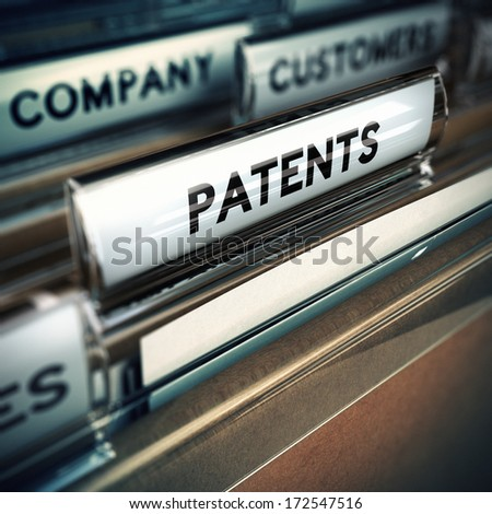 Folder and focus on a tab with the word patents, blur effect. Concept of company innovation.   - stock photo