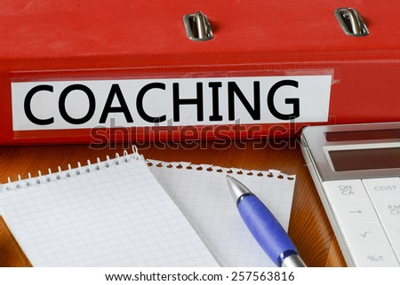 Folder with label coaching. Folder with label coaching and notepad, pen and calculator - stock photo