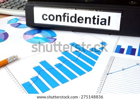 Folder with the label confidential and charts - stock photo