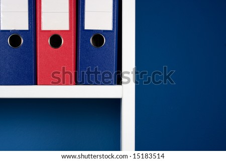 Folders for documents in white bookcase - stock photo