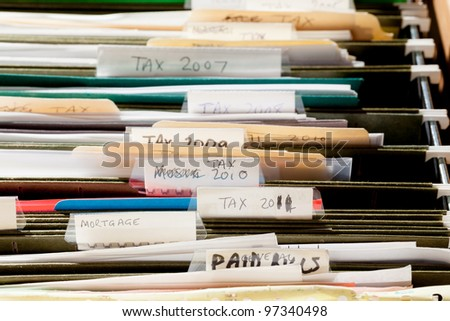 Folders in file drawer sorted into tax years and mortgage documents