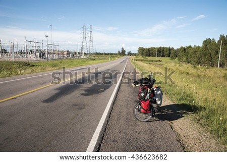 Folding bicycle with panniers in a empty road,Uruguay