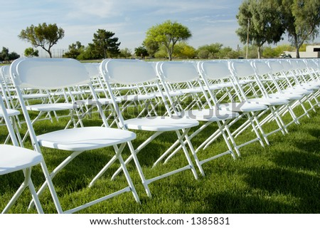 Folding Chairs And Stage Set Up For An Outdoor College Graduation Ceremony.