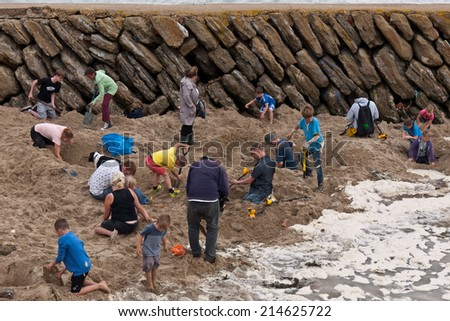 FOLKESTONE, UK-AUGUST 30: People dig in Folkestone Harbour beach, to search for gold buried by Berlin based artist Michael Sailstorfer. The event is part of the Triennial. August 30 2014 Folkestone UK - stock photo