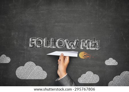 Follow me concept on black blackboard with businessman hand holding paper plane - stock photo