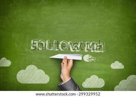 Follow me concept on green blackboard with businessman hand holding paper plane - stock photo