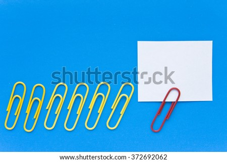 Follow me, leader concept - red paperclip leading a group of yellow paperclips with a paper card for your text - stock photo