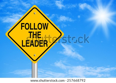 Follow the leader text is on road sign with blue sky background.