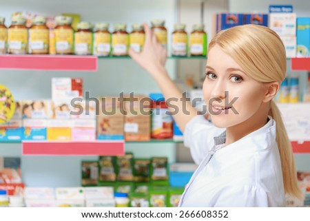 Follow the prescription. Young blonde pharmacist picking medicine and drugs from shelves in the drugstore - stock photo