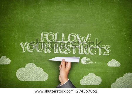 Follow your instincts concept on green blackboard with businessman hand holding paper plane - stock photo