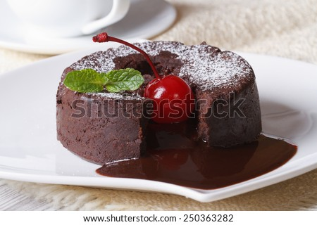 fondant chocolate cake with cherries and mint close up on a plate and coffee. horizontal  - stock photo