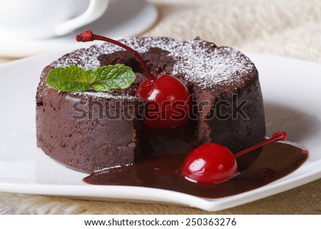 fondant chocolate cake with cherries and mint macro on a plate and coffee. Horizontal  - stock photo