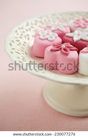 Fondant-covered petit fours on vintage style cake stand - stock photo