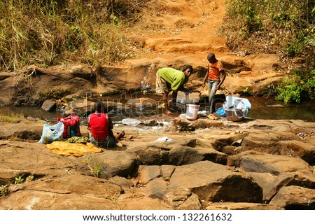 FONGO-TONGO, CAMEROON - JANUARY 20: African  woman with  men washing clothes in a river on January 20, 2013 in Fongo Cameroon. Fresh water is not available in most rural household in Cameroon. - stock photo