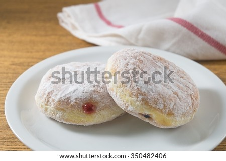 Food and Bakery, Two Delicious Sweet Donuts Strawberry Jam and Blueberry Jam with Icing Toppings. - stock photo