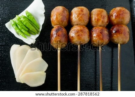 Food and Cuisine, Delicious Thai Grilled Sausages on Wooden Skewer Served with Pickled Ginger, Cabbage and Chili Pepper. - stock photo