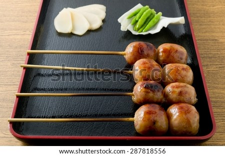 Food and Cuisine, Plate of Thai Grilled Sausages on Wooden Skewer Served with Pickled Ginger, Cabbage and Chili Pepper. - stock photo