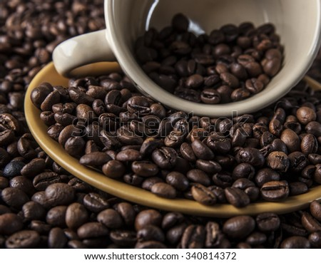 Food and drink background of yellow mug full of coffee beans. - stock photo