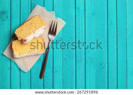 Food and drink, still life concept. Slices of home made orange cake on a wooden table. Selective focus, top view, copy space background - stock photo