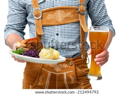 Food and drinks are served by waiter wearing traditional Bavarian leather trousers - stock photo