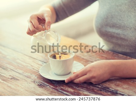 food and home concept - close up of female pouring milk into coffee - stock photo