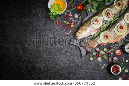 Food background for fish dishes cooking with various ingredients. Raw char with oil, herbs and spices on cutting board , top view.Healthy food or diet nutrition concept. - stock photo