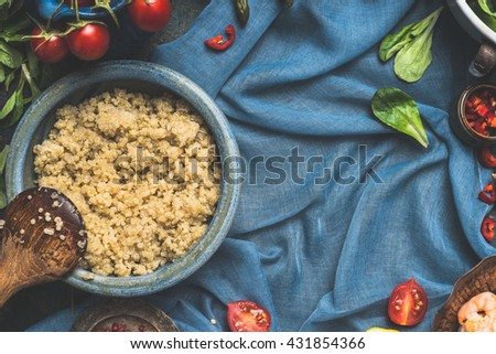 Food background for Quinoa recipes and cooking. Cooked quinoa with wooden spoon and vegetables ingredients on dark blue background, top view, place for text. Superfood concept. - stock photo