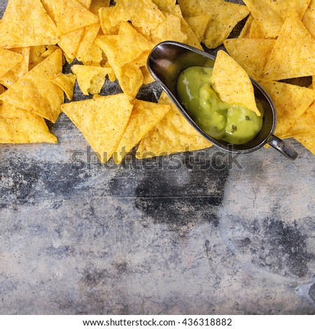 Food background. Mexican nachos chips with guacomole sauce over old textured tin background. Top view. With space for text. Square image