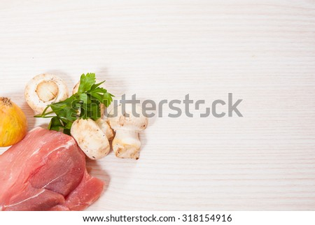 Food background of fresh meat, mushrooms, onion at the wooden board with copy space - stock photo