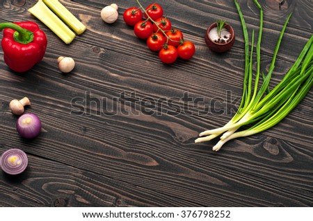 Food background. On a dark wooden surface, cherry tomatoes, green onions, bulb onion, mushrooms and peppers. Top view with space for text or object - stock photo