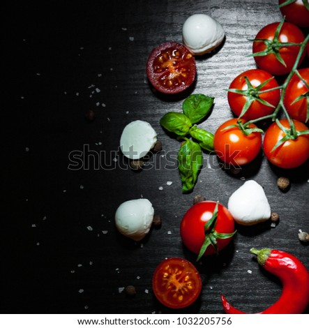 food background. red chili peppers, cherry tomato, basil, black pepper, mozzarella balls, salt on dark wooden background with copy space. top view