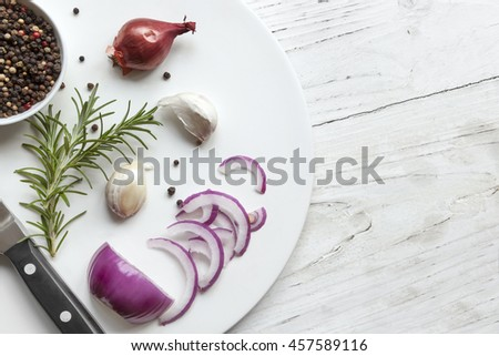 Food background top view, with red onion, rosemary, garlic, peppercorns over rustic timber.