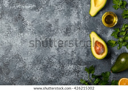 Food background with avocado, lemon, parsley and olive oil on concrete surface, top view, copy space. - stock photo