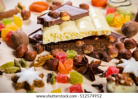Food background with candies, nuts, cookies, chocolate, dried fruits and other sweets, selective focus