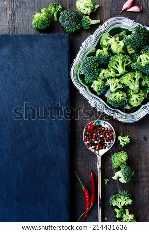 Food background with fresh green broccoli and spices. Slate and wood background with copyspace. Top view. - stock photo
