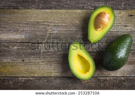 food background with fresh organic avocado on  old wooden table, top view, copy space - stock photo