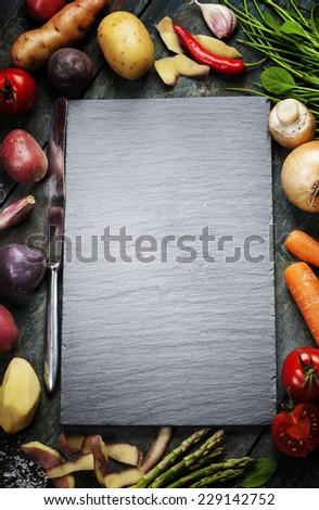 Food background, with fresh vegetables. Slate and wood background.  - stock photo