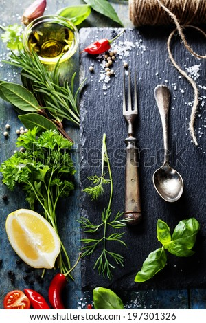 Food background, with herbs, spices, olive oil, salt, lemons and vegetables. Slate and wood background.  - stock photo