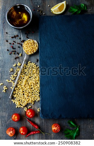 Food background, with raw pasta, herbs, spices, olive oil, salt, lemons and vegetables. Slate and wood background. Top view. - stock photo