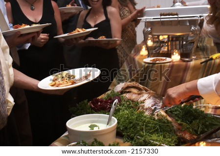 Food being served buffet style during a wedding event. This was shot with a slow shutter speed, and there is some movement noticeable. - stock photo