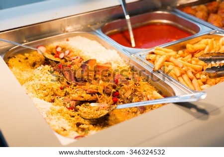 food, catering, self-service and eating concept - close up of rice pilaf and other dishes on metallic tray - stock photo