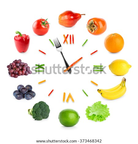Food clock with fruits and vegetables on white background. Food concept
