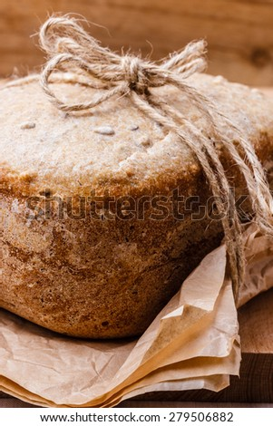 Food. Closeup freshly baked loaf of bread on baking paper - stock photo