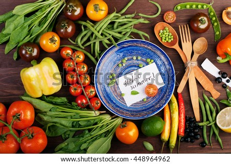 Food concept 'Hello, summer!'. Juicy bright summer vegetable background, which lie around a blue plate. Multicolored tomatoes, peppers, young peas, green beans, spinach and other herbs and vegetables - stock photo