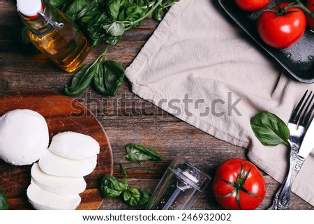 Food, cooking. Mozzarella with tomato on the table - stock photo