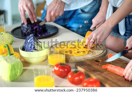 Food cooking together. Close-up view of the hands of young smiling loving couple cook dinner or breakfast in the kitchen while cut fruits and vegetables in the kitchen in the apartment - stock photo