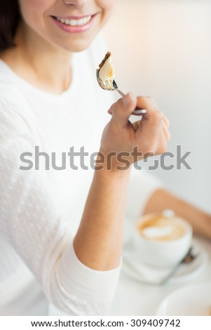 food, dessert, people and lifestyle concept - close up of smiling young woman holding fork and eating cake at cafe or home - stock photo