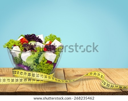 Food. Diet meal. Vegetables salad in a bowl with measuring tape - stock photo