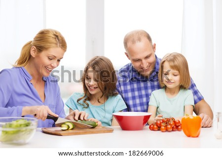 food, family, children, hapiness and people concept - happy family with two kids making dinner at home - stock photo